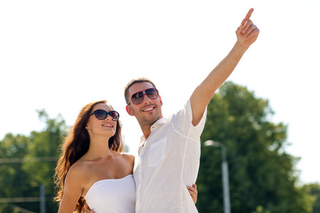 love, travel, tourism, people and friendship concept - smiling couple wearing sunglasses hugging and pointing finger in park photo
