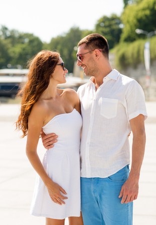 love, travel, tourism, people and friendship concept - smiling couple wearing sunglasses hugging in city photo