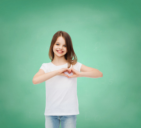 advertising, gesture, charity, education and people - smiling little girl in white blank t-shirt over green board background