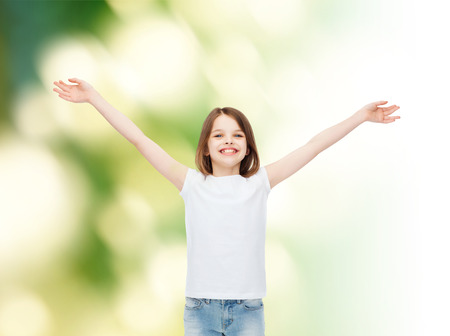 stretched out: advertising, childhood, gesture, ecology and people - smiling little girl in white blank t-shirt with stretched out arms over green background Stock Photo