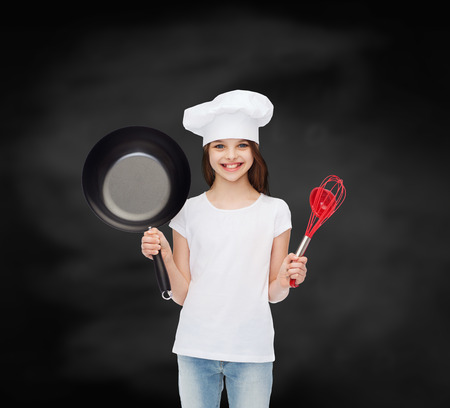 advertising, childhood, cooking, education and people - smiling girl in white t-shirt and cooking hat holding pan over blackboard background