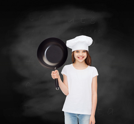 advertising, childhood, cooking, education and people - smiling girl in white t-shirt and cooking hat holding pan over blackboard background photo