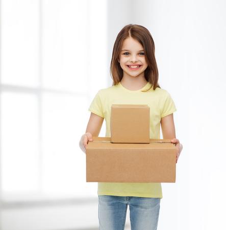 sala parto: pubblicit�, infanzia, consegna, posta e persone - sorridente bambina in possesso di scatole di cartone su sfondo bianco camera