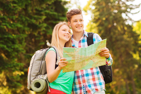 tourism and friendship concept - smiling couple with map and backpack in forest photo