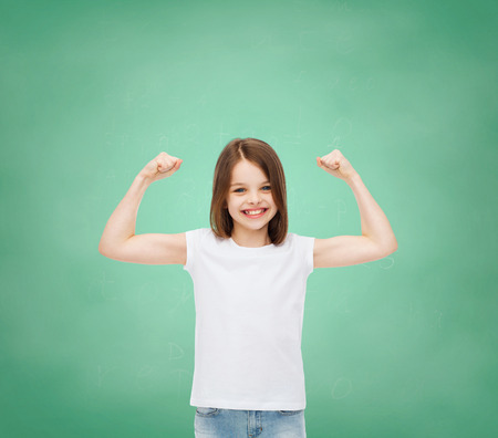 strong girl: advertising, gesture, school, education and people - smiling little girl in white blank t-shirt with raised arms over green board background Stock Photo