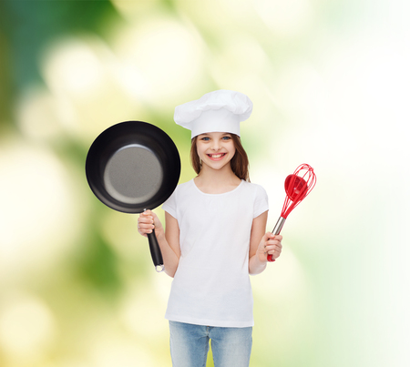 advertising, childhood, cooking and people - smiling girl in white t-shirt and cooking hat holding pan over green background photo