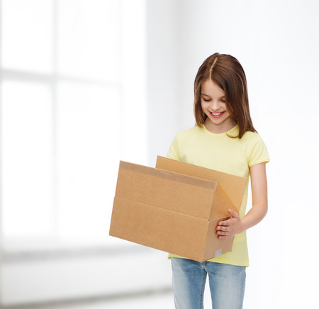 delivery room: advertising, childhood, delivery, mail and people - smiling girl holding open cardboard box and looking into it over white room background Stock Photo