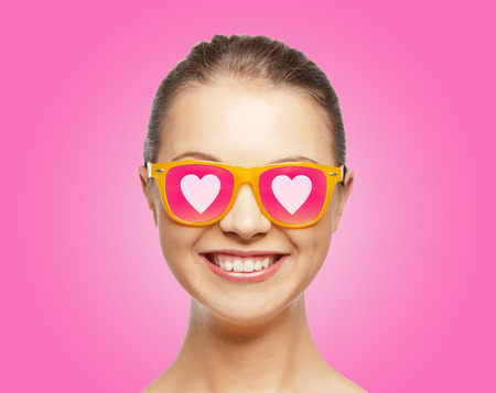 love, happiness, valentines day, face expressions and people concept - portrait of smiling teenage girl in pink sunglasses with hearts photo