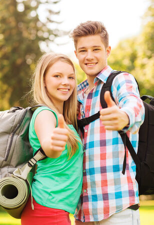 travel, vacation, tourism, gesture and friendship concept - smiling couple with backpacks showing thumbs up in nature photo