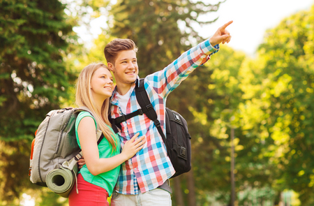 travel, vacation, tourism and friendship concept - smiling couple with backpacks pointing finger in nature photo
