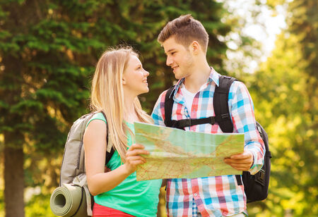 travel, vacation, tourism and friendship concept - smiling couple with map and backpacks looking at each other in forest photo