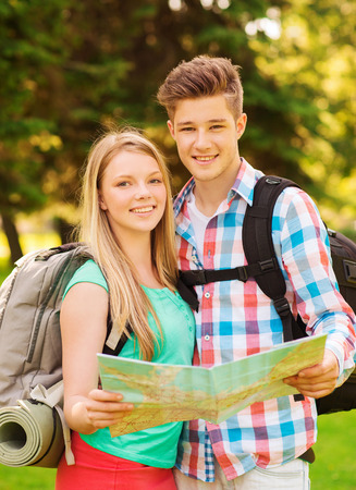travel, vacation, tourism and friendship concept - smiling couple with map and backpack in forest photo