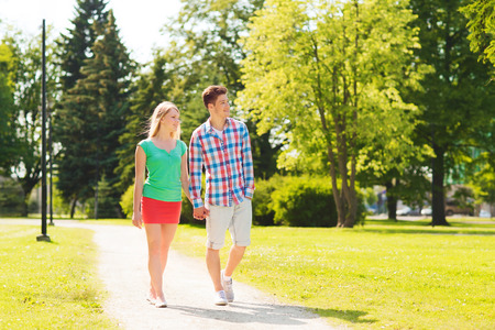out in town: holidays, vacation, love and friendship concept - smiling couple walking and holding hands in park Stock Photo