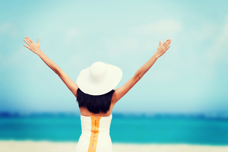 summer holidays and vacation - girl with hands up on the beach photo