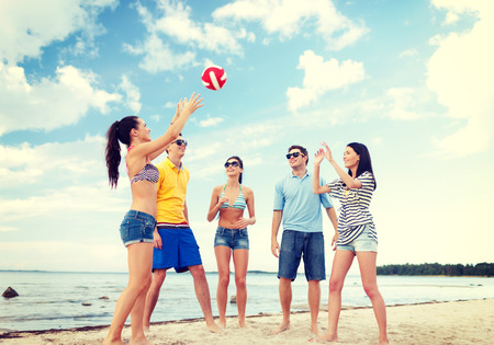 beach volleyball: summer, holidays, vacation, happy people concept - group of friends having fun on the beach