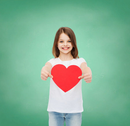 childhood, cahrity, education, love and people concept - smiling little girl sitting with red heart cutout over green blackboard background photo