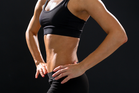 athletic wear: fitness and diet concept - close up of beautiful athletic female abs in sportswear