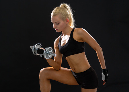 fitness, healthcare and dieting concept - young sporty woman with heavy steel dumbbell