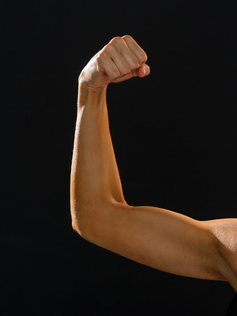 strong arm: fitness and diet concept - close up of athletic woman flexing her biceps
