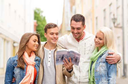 travel, vacation and friendship concept - group of smiling friends with city guide exploring town photo