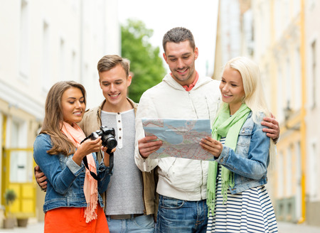 travel, vacation, technology and friendship concept - group of smiling friends with map and photocamera exploring city photo