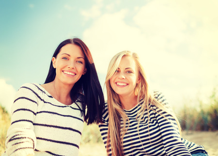 summer, holidays, vacation, happy people concept - smiling girlfriends having fun on the beach