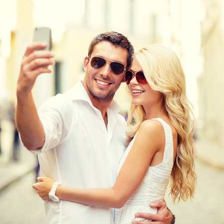 summer holidays, technology, love, relationship and dating concept - smiling couple taking selfie with smartphone in the city photo