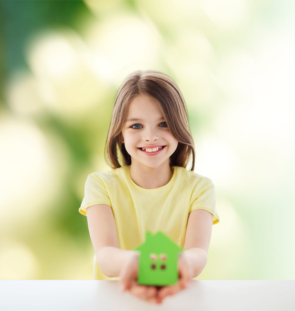 education loan: home, education, nature, childhood and people concept - beautiful little girl sitting at table holding white house cutout over green background Stock Photo