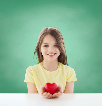 childhood, love, charity, education and people concept - smiling little girl sitting and holding red heart over green blackboard background photo