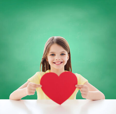 childhood, charity, education, love and people concept - smiling little girl sitting with red heart cutout over green blackboard background photo