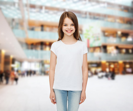 advertising, childhood, consumerism and people - smiling little girl in white blank t-shirt over shopping center background photo