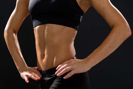 six pack: fitness and diet concept - close up of beautiful athletic female abs in sportswear