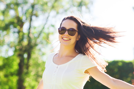 protective spectacles: summer, leisure, vacation and people concept - smiling young woman wearing sunglasses standing in park Stock Photo