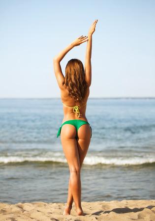 culo di donna: vacanze, vacanze e persone estate concetto - giovane donna prendere il sole sulla spiaggia