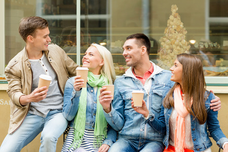 out in town: friendship, travel, drink and vacation concept - group of smiling friends with take away coffee