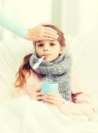 healthcare and medicine concept - ill girl child with thermometer in mouth, cup of hot tea and caring mother photo