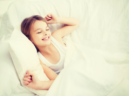 rested: health, beauty and childhood concept - smiling girl child waking up in bed at home Stock Photo