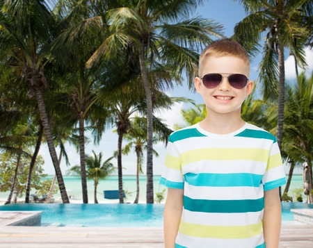childhood, summer, travel, vacation and people concept - smiling little boy wearing sunglasses over pool and beach background photo