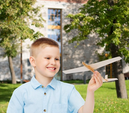 dreams, future, hobby, education and childhood concept - smiling little boy holding wooden airplane model in his hand over yard background photo