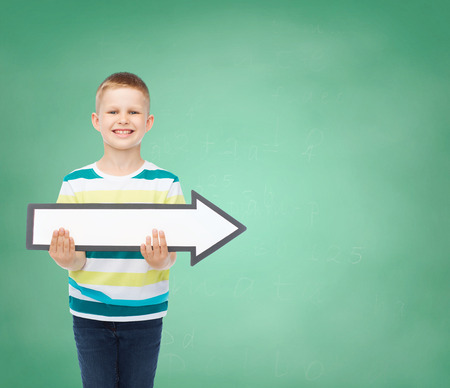 directive: advertising, direction, education and childhood concept - smiling little boy with white blank arrow over green board background Stock Photo