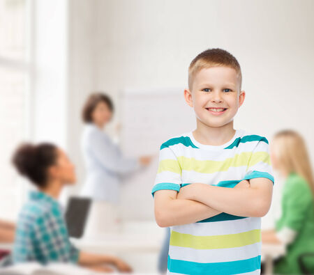 kids class: childhood, school, education and people concept - smiling little boy in casual clothes with crossed arms over group of students in classroom Stock Photo