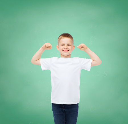 arms raised: childhood, gesture, education, advertisement and people concept - smiling boy in white t-shirt with raised hands over green board background Stock Photo