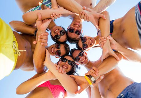friendship, summer vacation, teamwork and people concept - group of smiling friends wearing swimwear standing in circle over blue sky holding hands connected to each other photo
