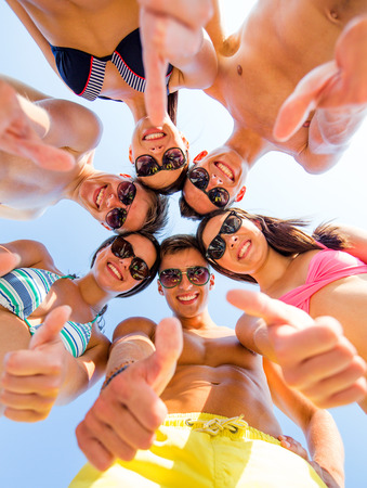 friendship, summer vacation, holidays, gesture and people concept - group of smiling friends wearing swimwear standing in circle and showing thumbs up over blue sky photo