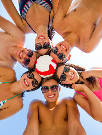 beach volleyball: friendship, happiness, summer vacation, holidays and people concept - group of smiling friends wearing swimwear standing in circle with volleyball over blue sky Stock Photo