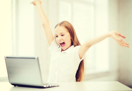 computer lesson: education, school, technology and internet concept - happy little girl with laptop pc at school Stock Photo