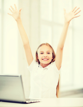 internet education: education, school, technology and internet concept - happy little girl with laptop pc at school Stock Photo