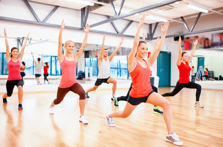 gym class: fitness, sport, training, gym and lifestyle concept - group of smiling people stretching in the gym Stock Photo