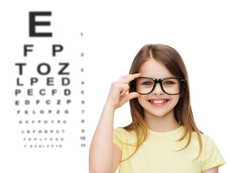 vision problems: education, school and vision concept - smiling cute little girl in black eyeglasses
