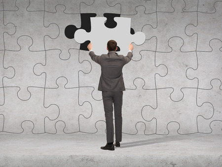 back link: business, development and people concept - businessman in suit setting piece of puzzle to the wall background Stock Photo